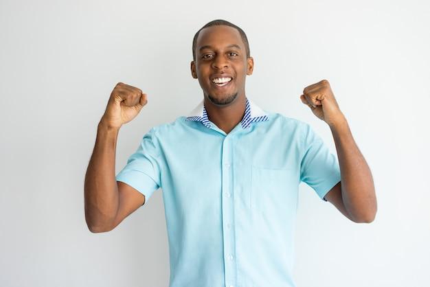 Netter hübscher afrikanischer kerl im hemd der kurzen ärmel, das ja geste macht