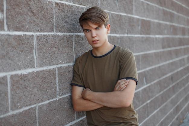 Netter hübscher junger mann in einem grünen t-shirt mit einer modischen frisur, die in der nähe einer weinsteinmauer steht