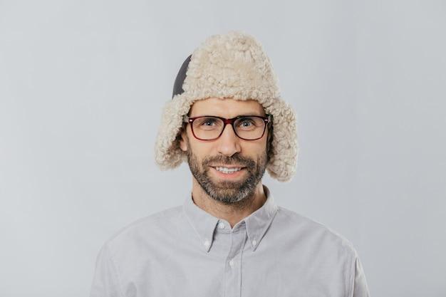 Netter hübscher kerl trägt warme winterkappe mit ohrenklappen, schauspielen und weißem hemd