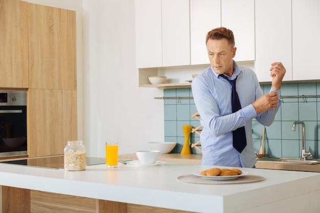 Netter hübscher kluger geschäftsmann, der in der küche steht und frühstück vorbereitet, während er sich auf arbeit vorbereitet
