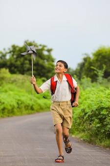 Netter indischer junge, der mit einem windrad spielt