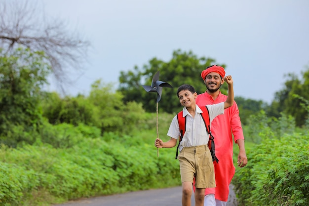 Netter indischer junge, der mit seinem vater mit einem windrad spielt