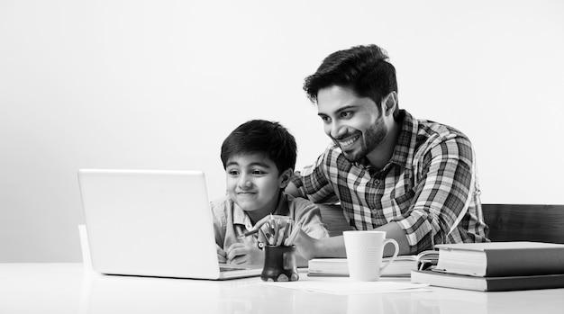 Netter indischer junge mit vater oder männlichem tutor, der zu hause mit laptop und büchern hausaufgaben macht - online-schulungskonzept