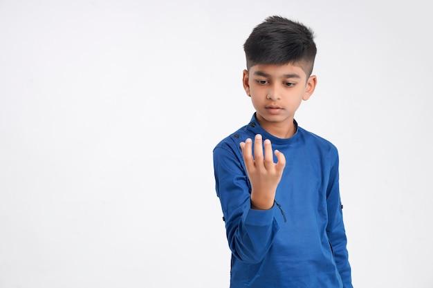 Netter indischer kleiner junge, der auf finger zählt