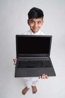 Netter indischer kleiner junge, der laptop-bildschirm zeigt
