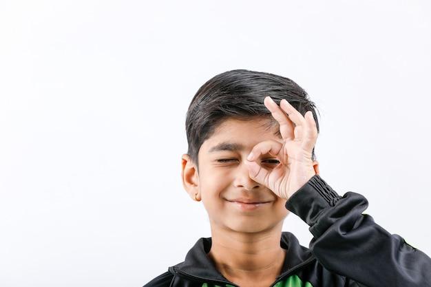 Netter indischer kleiner junge, der mehrfachen ausdruck spielt und gibt