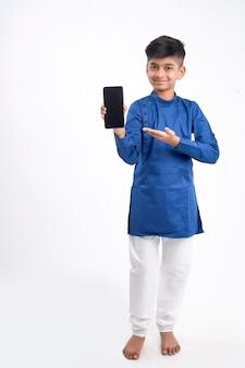 Netter indischer kleiner junge, der smartphonebildschirm auf weiß zeigt