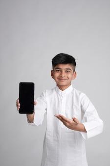 Netter indischer kleiner junge, der smartphonebildschirm mit kopienraum über weißem hintergrund zeigt