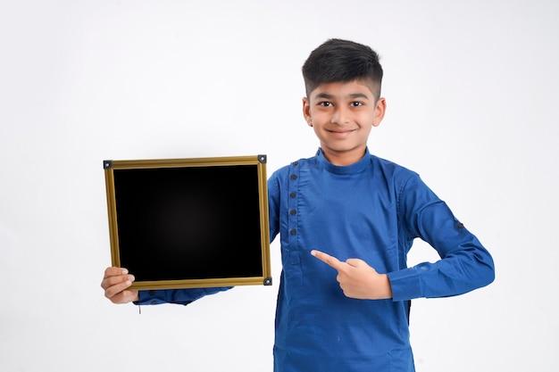 Netter indischer kleiner junge, der tafel mit kopienraum über weißem hintergrund zeigt