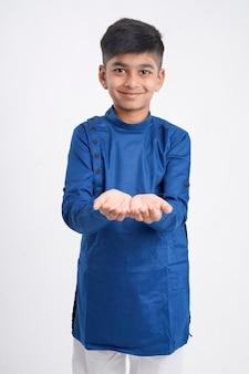 Netter indischer kleiner junge in ethnischer abnutzung und ausdruck auf weiß zeigend