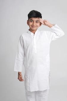 Netter indischer kleiner junge in ethnischer abnutzung und ausdruck über weißem hintergrund zeigend