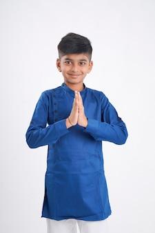 Netter indischer kleiner junge in namaste oder betender pose auf weiß