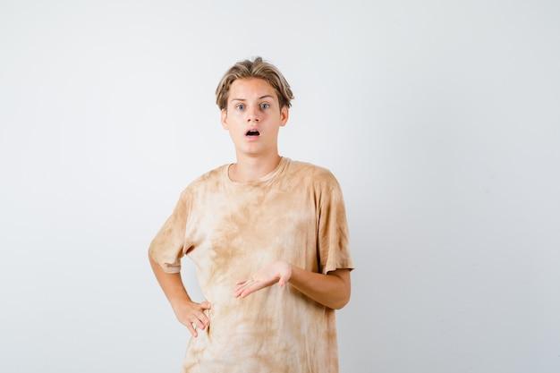 Netter jugendlich junge, der palme in fragender geste im t-shirt ausbreitet und verwirrt schaut. vorderansicht.