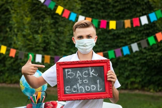 Netter jugendlich junge in der medizinischen maske, die mit kleiner schulbehörde aufwirft