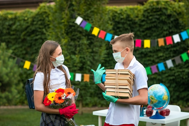 Netter jugendlich junge und mädchen an medizinischen masken und handschuhen, die bücher und blumen halten und draußen sprechen