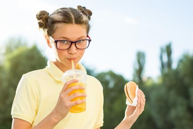 Netter jugendlicher, der hamburger und orangensaft hält