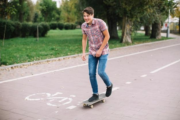 Netter jugendlicher, der nahe fahrradweg skateboard fährt
