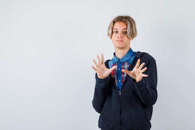 Netter jugendlicher junge, der kapitulationsgeste in hemd, hoodie zeigt und zögerlich, vorderansicht schaut.
