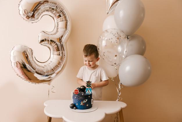 Netter junge 3 jahre alt feiert seinen geburtstag und isst einen köstlichen schönen kuchen, foto eines kindes mit luftballons