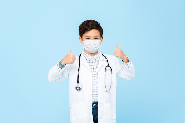 Netter junge arzt, der medizinische maske trägt und daumen auf hellblau isoliert aufgibt