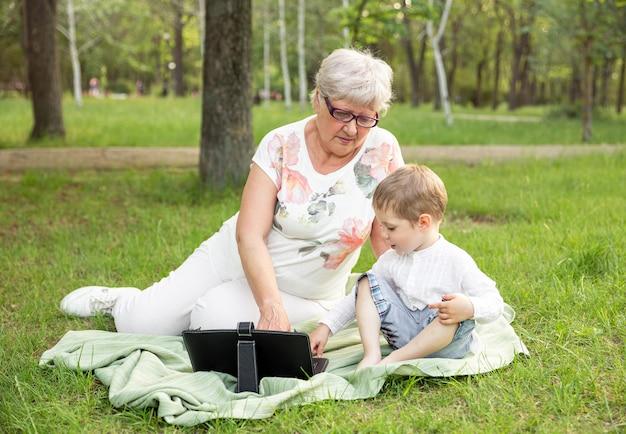 Netter junge bringt oma in gläsern bei, moderne intelligente geräte im freien zu verwenden