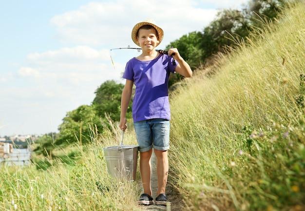 Netter junge, der am sommertag angeln geht