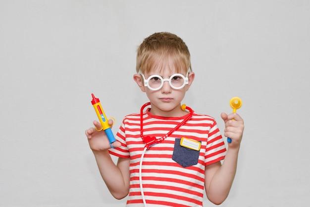 Netter junge, der arzt spielt. spielzeugspritze, brille und phonendoskop. porträt