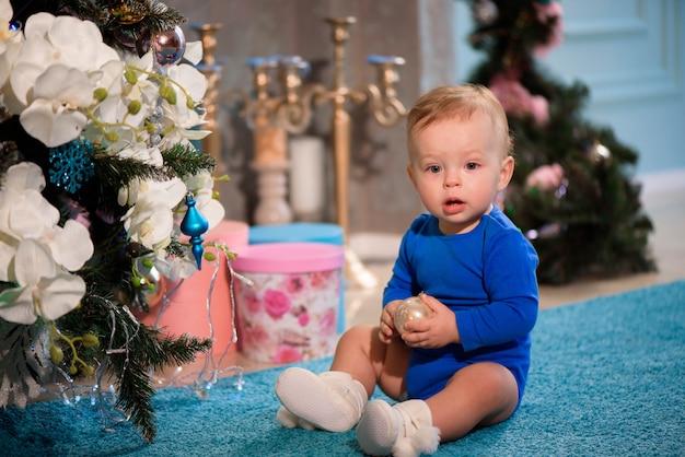 Netter junge, der auf dem teppich nahe weihnachtsbaum sitzt