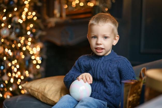 Netter junge, der auf der couch im hintergrund des weihnachtsbaums sitzt.