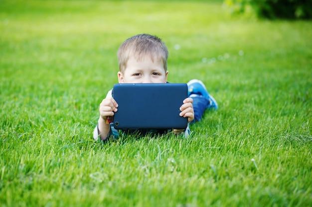 Netter junge, der auf gras im park liegt und tabletten-pc verwendet