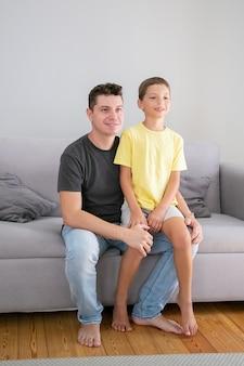 Netter junge, der auf papas schoß sitzt. vater und sohn sitzen auf der couch im wohnzimmer und schauen weg. familien- und elternschaftskonzept