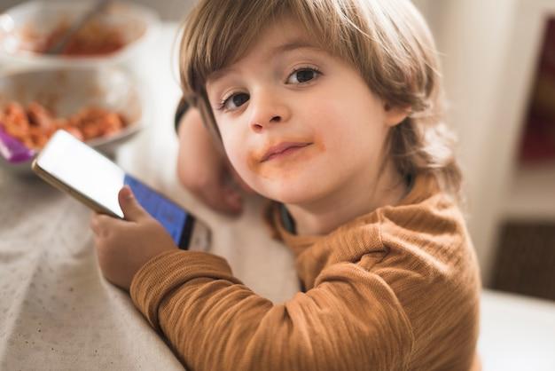 Netter junge, der bei tisch telefon hält