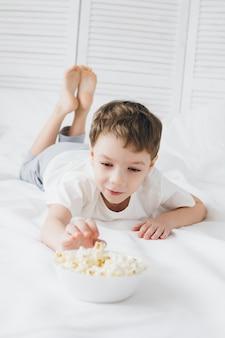 Netter junge, der das popcorn sitzt im bett mit weißer bettwäsche isst