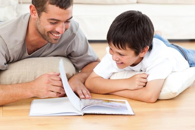 Netter junge, der ein buch mit seinem vater auf dem boden liest