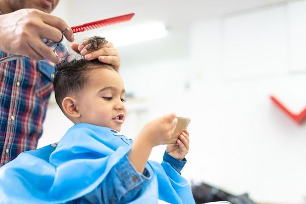Netter junge, der ein haar geschnitten in einen friseur shop beauty concept erhält