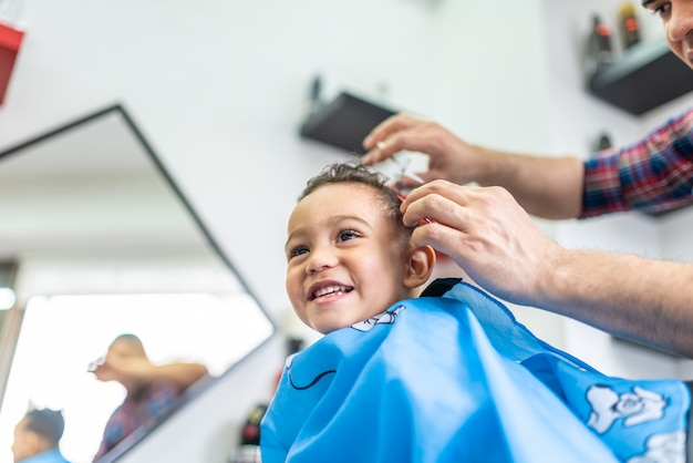 Netter junge, der ein haar geschnitten in einen friseursalon erhält. beauty-konzept.