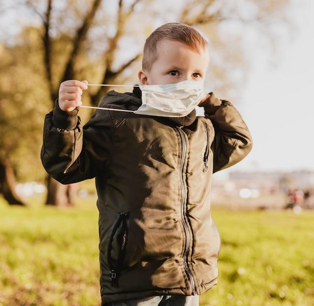 Netter junge, der eine medizinische maske im park trägt