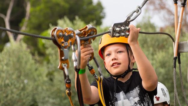 Netter junge, der einen sonnigen tag in einem kletterabenteuer-aktivitätspark genießt. junge bei kletteraktivität im hochseilwaldpark.