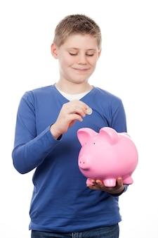 Netter junge, der geld in einem sparschwein spart