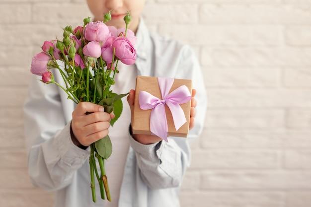 Netter junge, der geschenkbox und blumenstraußblumen für mutter a mit fallenden blütenblättern hält.