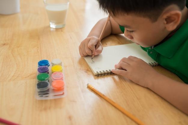 Netter junge, der hausaufgaben macht, seiten ausmalt, schreibt und malt. kinder malen. kinder zeichnen. vorschulkind mit büchern zu hause. vorschulkinder lernen schreiben und lesen. kreativer junge.