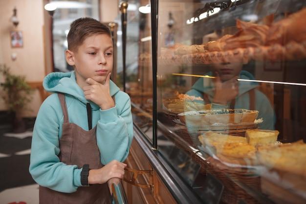Netter junge, der im bäckerei-café seiner eltern arbeitet und einzelhandelsanzeige untersucht