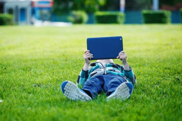 Netter junge, der im park liegt und tabletten-pc verwendet