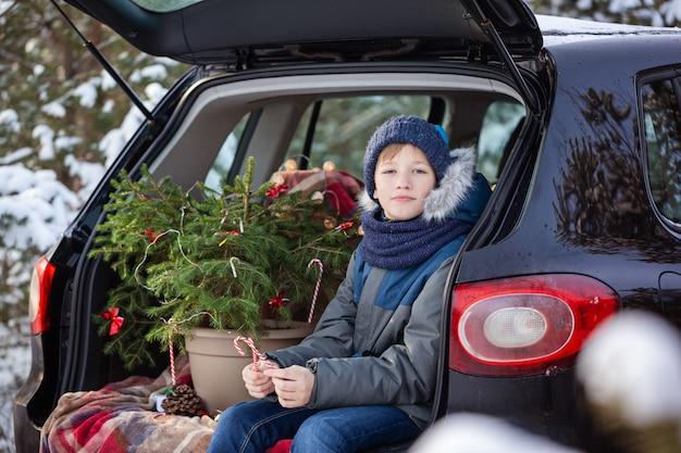 Netter junge, der im schwarzen auto am schneebedeckten winterwald sitzt. weihnachtskonzept.