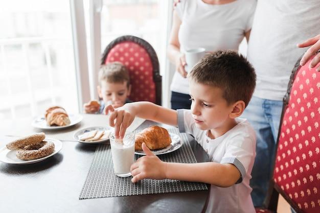 Netter junge, der keks im glas milch während des frühstücks eintaucht