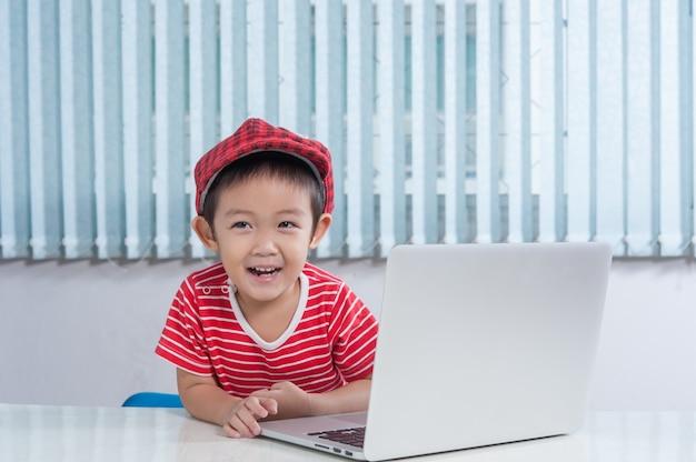 Netter junge, der labtop im kinderzimmer spielt