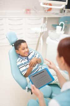 Netter junge, der lächelt. fröhlicher süßer junge, der lächelt, während er mit seinem freundlichen zahnarzt spricht?