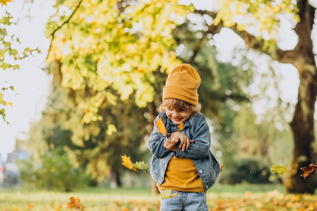 Netter junge, der mit blättern im herbstpark spielt