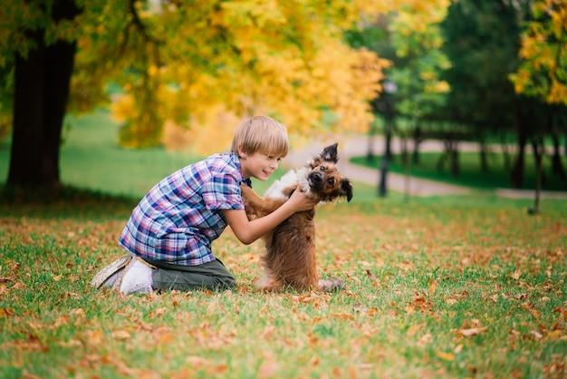 Netter junge, der mit seinem hund auf der wiese spielt und geht.