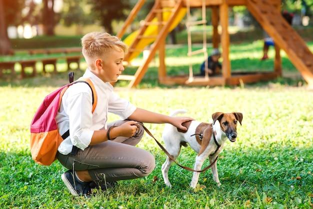 Netter junge, der mit seinem hund im park spielt.